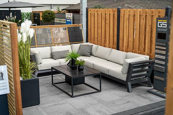 Prachtige lichtgrijze tegels met loungeset en schutting